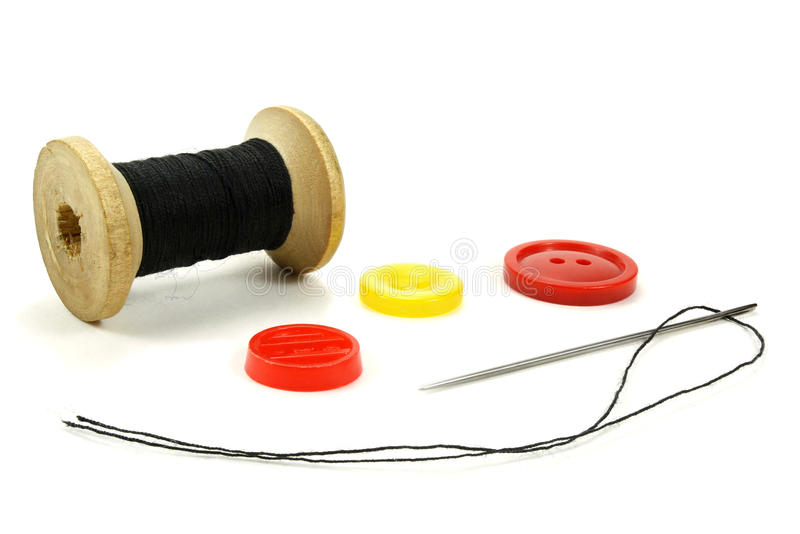 La bobina di legno con i fili, un ago e un colore si abbottona per il cucito su un fondo bianco immagini stock libere da diritti