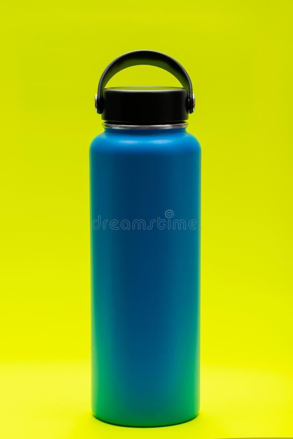 La boca ancha azul aisló la botella de acero inoxidable con el casquillo plano ancho aislado en amarillo brillante BPA-libre Pare imágenes de archivo libres de regalías