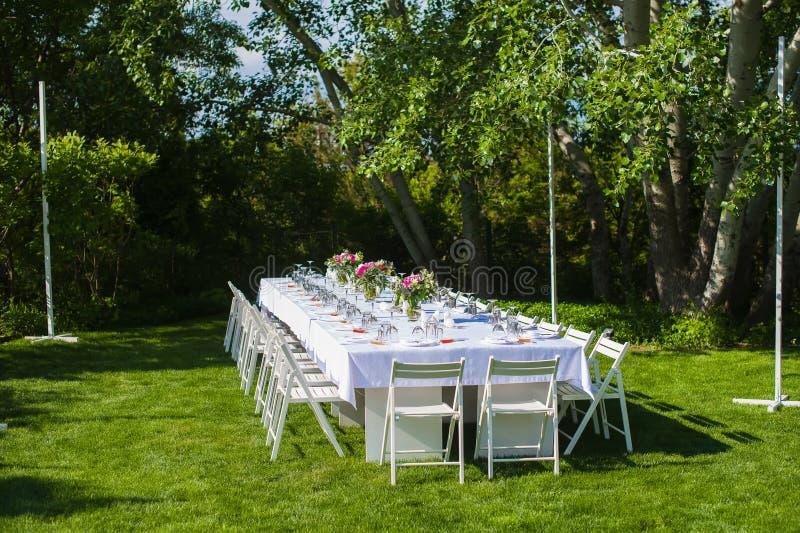 La boda blanca y larga adornó la tabla al aire libre imagen de archivo