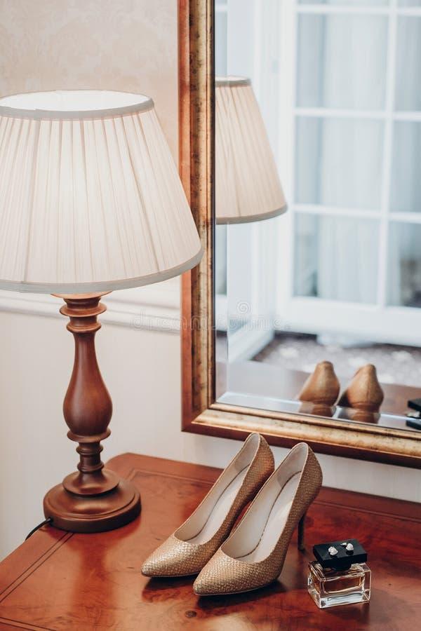 La boda de lujo calza perfume y los pendientes costosos en roo del hotel fotos de archivo libres de regalías
