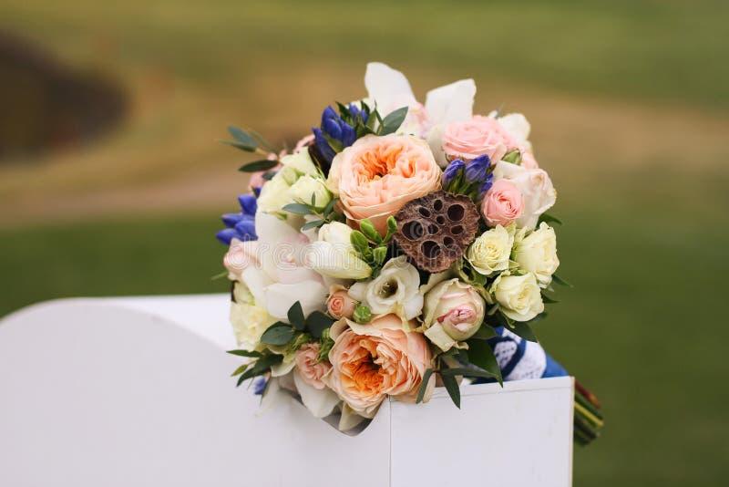 La boda florece en un fondo de la hierba verde en un pedestal blanco imagen de archivo libre de regalías