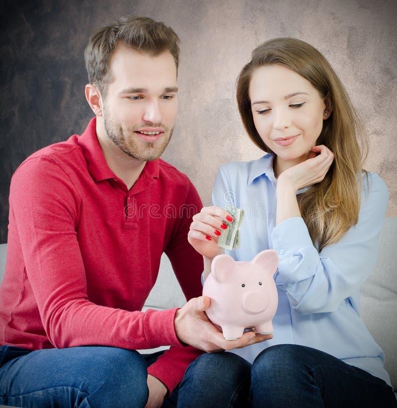 La boda joven pone ahorros en la hucha fotos de archivo libres de regalías