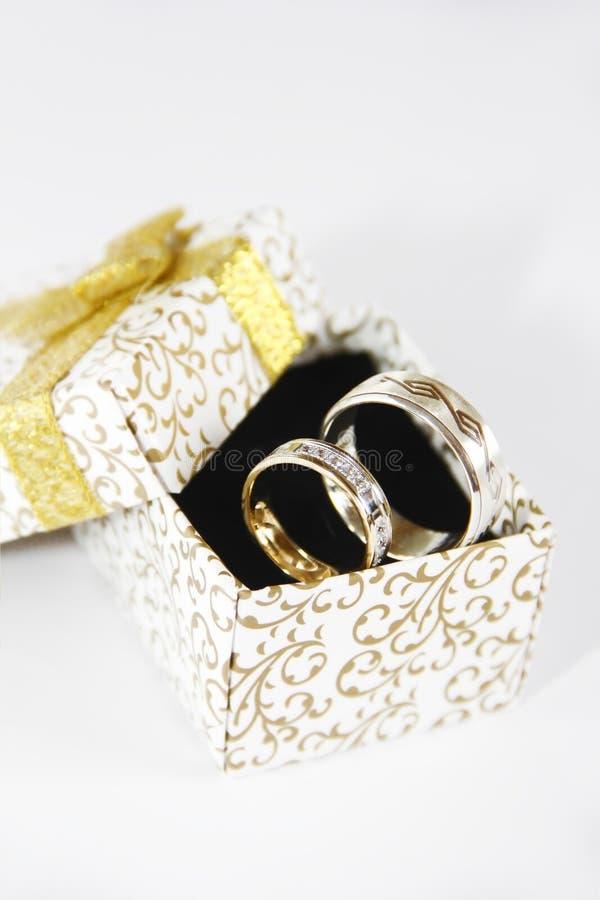 La bodas de plata del oro suena en una caja de regalo en un fondo negro imagen de archivo