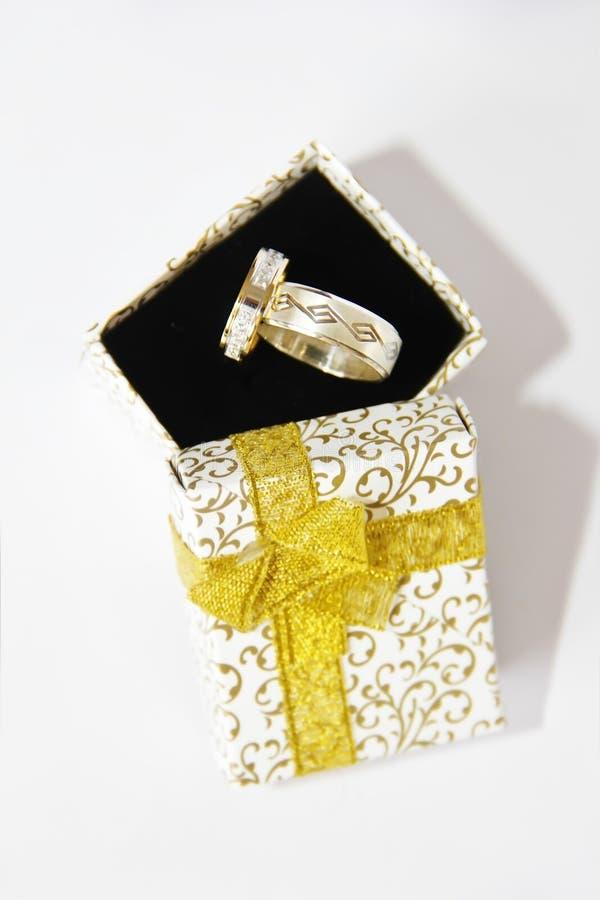 La bodas de plata del oro suena en una caja de regalo en un fondo negro fotos de archivo