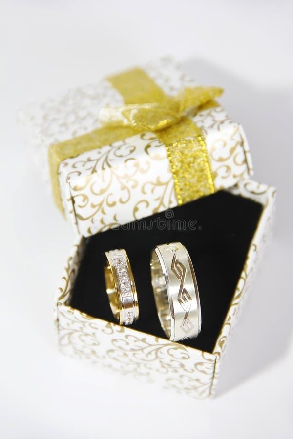 La bodas de plata del oro suena en una caja de regalo en un fondo negro imagenes de archivo