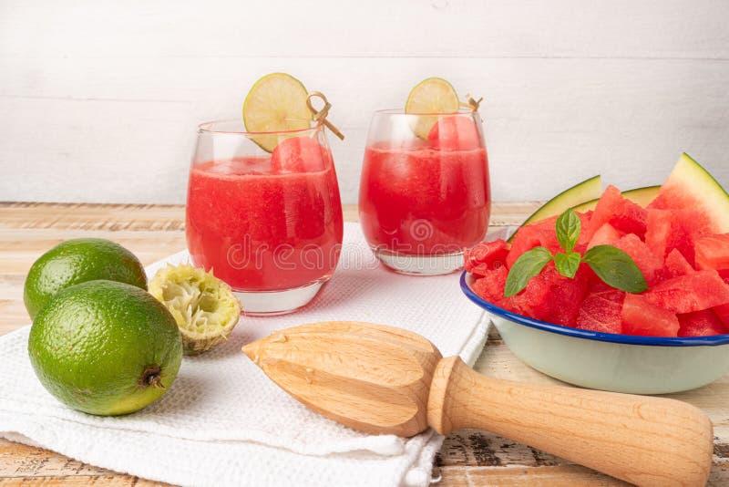 La boisson froide d'été fruité, le jus fait maison de pastèque ou le smoothie ont servi avec la chaux et les feuilles en bon état image stock