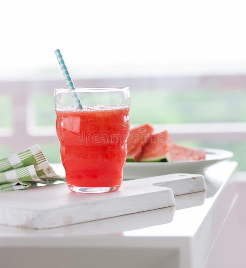 La boisson froide juteuse faite maison avec la pastèque et l'eau dans un verre avec la paille bleue sur une coupe en bois embarqu image stock