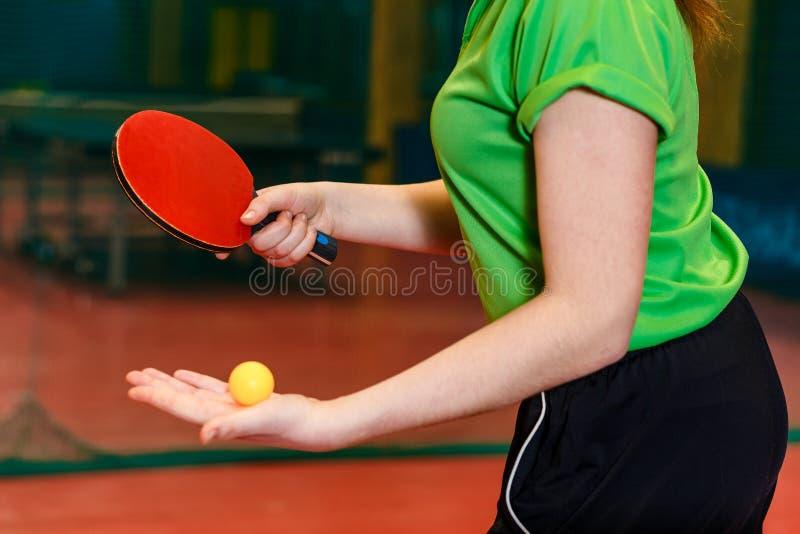 La bola anaranjada para los tenis de mesa miente en la palma de un atleta joven el principio del cierre del ping-pong del juego fotos de archivo libres de regalías