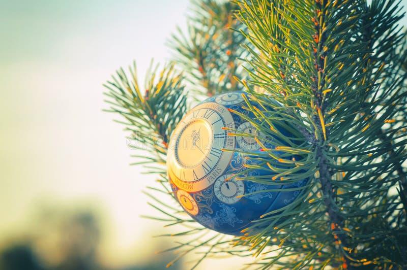 La bola de cristal, decoración de la Navidad con un reloj en un árbol de navidad, procesando debajo de una foto del vintage, text foto de archivo