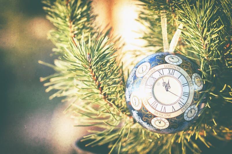 La bola de cristal, decoración de la Navidad con un reloj en un árbol de navidad, procesando debajo de una foto del vintage, text imagen de archivo libre de regalías