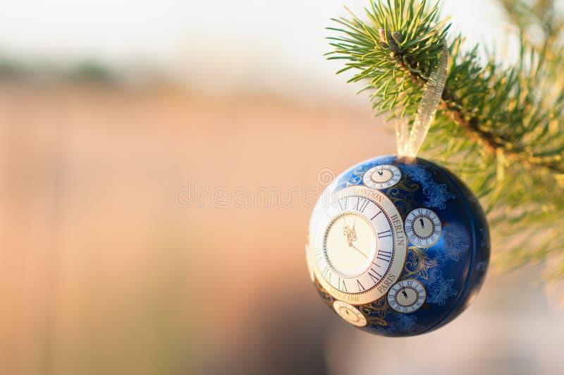 La bola de cristal, decoración de la Navidad con un reloj en un árbol de navidad, procesando debajo de una foto del vintage, text foto de archivo libre de regalías