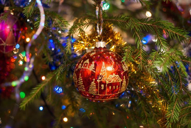 La bola de cristal roja del juguete de la Navidad, pintada con oro, cuelga en el fi foto de archivo