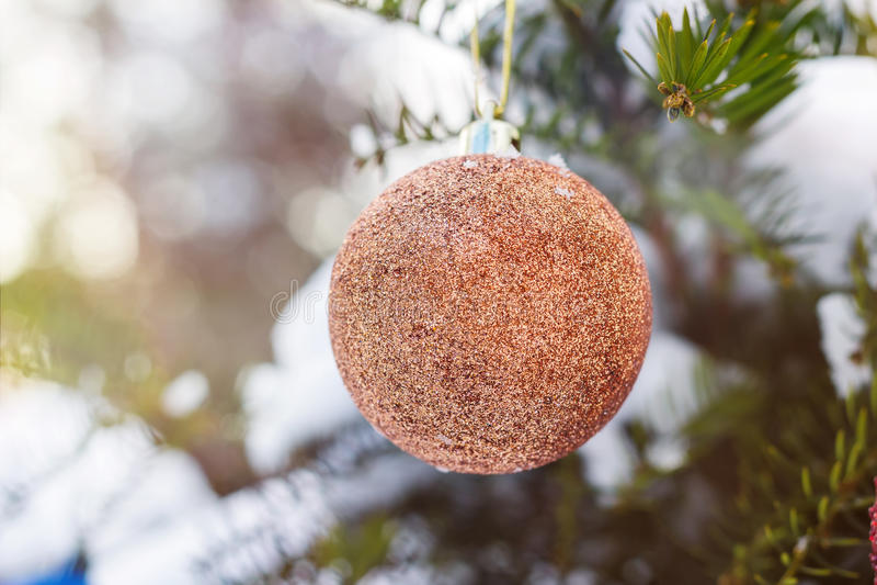 La bola de la Navidad del oro en la rama del abeto cubrió nieve La Navidad foto de archivo libre de regalías