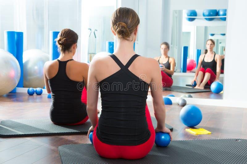 La bola de tono azul en pilates de las mujeres clasifica vista posterior imagen de archivo