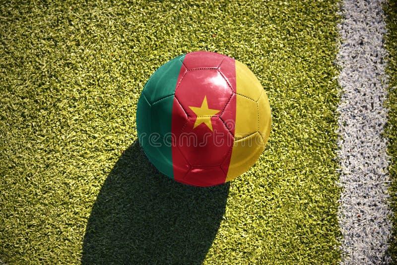 La bola del fútbol con la bandera nacional del Camerún miente en el campo imagen de archivo