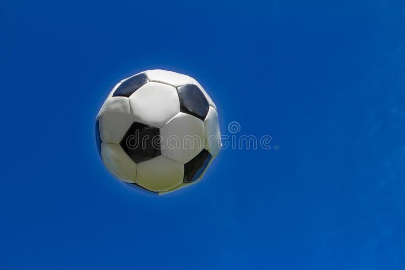 La bola del fútbol está volando en el cielo fotos de archivo