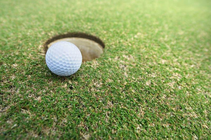 La bola en el agujero en el campo de golf fotografía de archivo libre de regalías