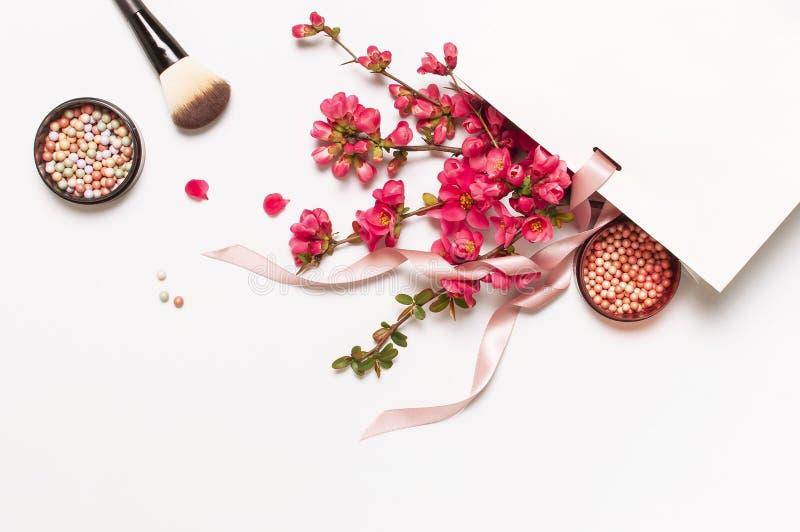 La bola se ruboriza colorete y hace frente al polvo, cepillo del maquillaje, flores del rosa de la primavera en el paquete blanco foto de archivo libre de regalías