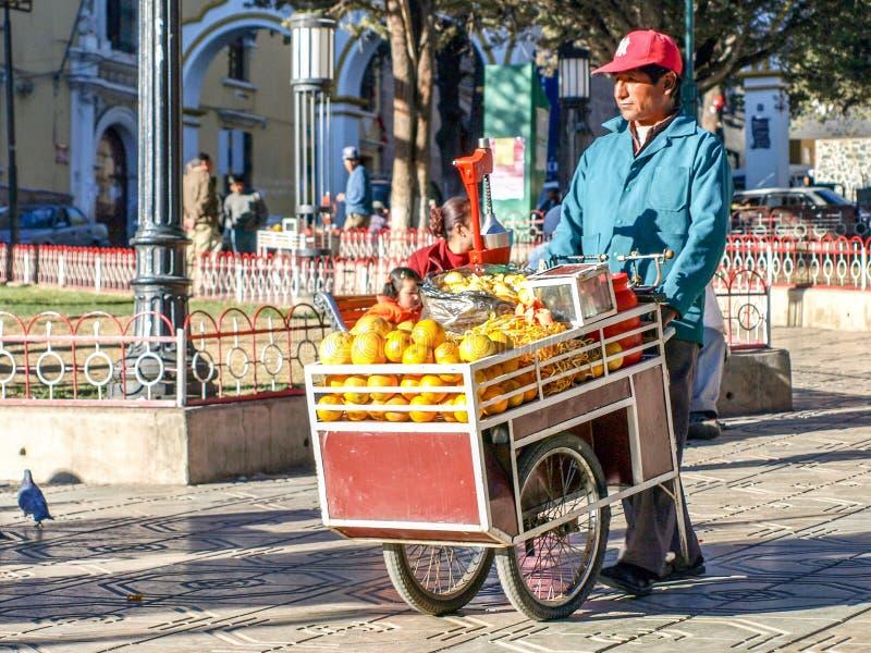 LA BOLIVIA, POTOSI, IL 4 LUGLIO 2008: Venditore del succo d'arancia della via con il piccolo trasporto in Potosi, Bolivia, Sudame fotografia stock