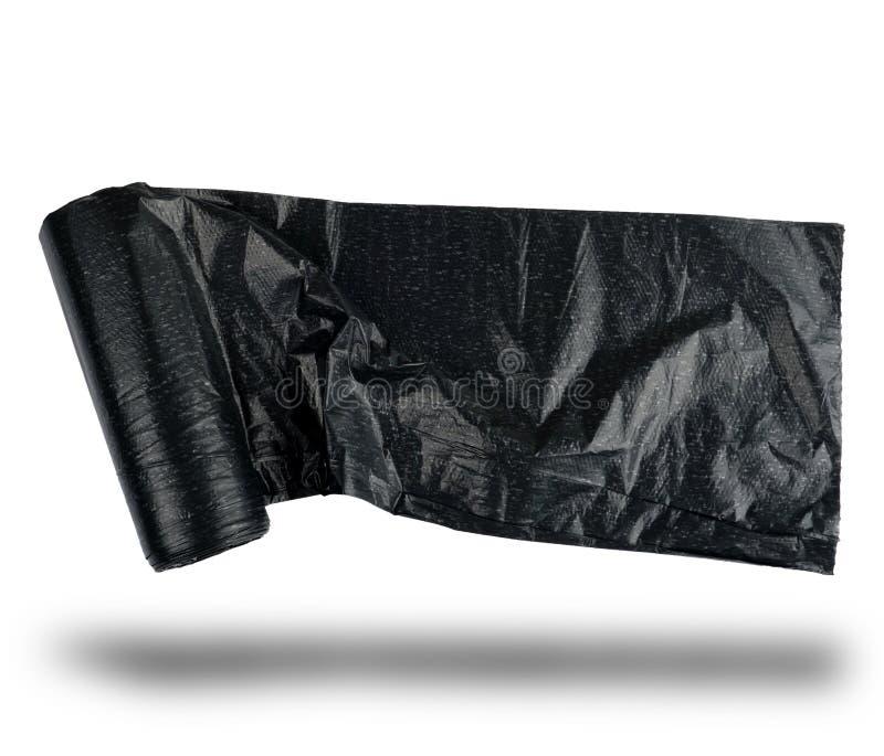 la bolsa de plástico negra del rollo para la basura en un fondo blanco foto de archivo libre de regalías