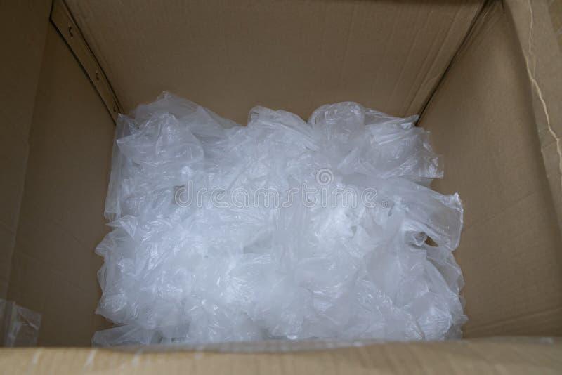 La bolsa de plástico usada en caja de papel foto de archivo