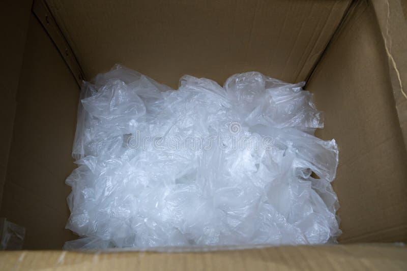La bolsa de plástico usada en caja de papel imagenes de archivo