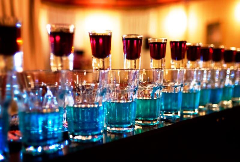 La bomba azul bebe los vasos de medida que se colocan en caer contraria imagenes de archivo