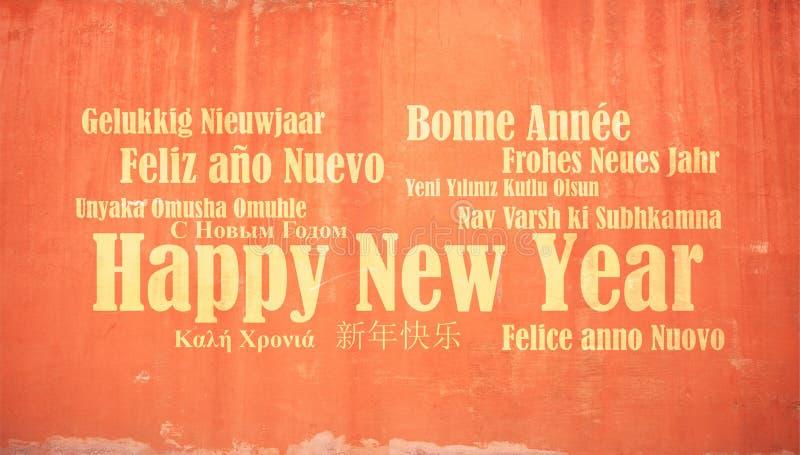La bonne année dans beaucoup de langues sur le stuc a peint le fond de mur photos libres de droits