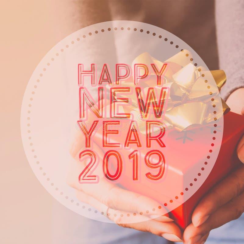 La bonne année 2019, typographie sur l'image remet tenir le boîte-cadeau photographie stock