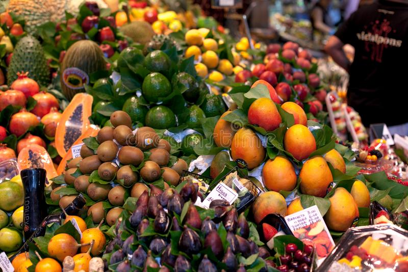 La Boqueria market in the Barcelona, Spain. Stall of avocado, papaya,figs, peach, mango and other exotic fruits at world royalty free stock photo