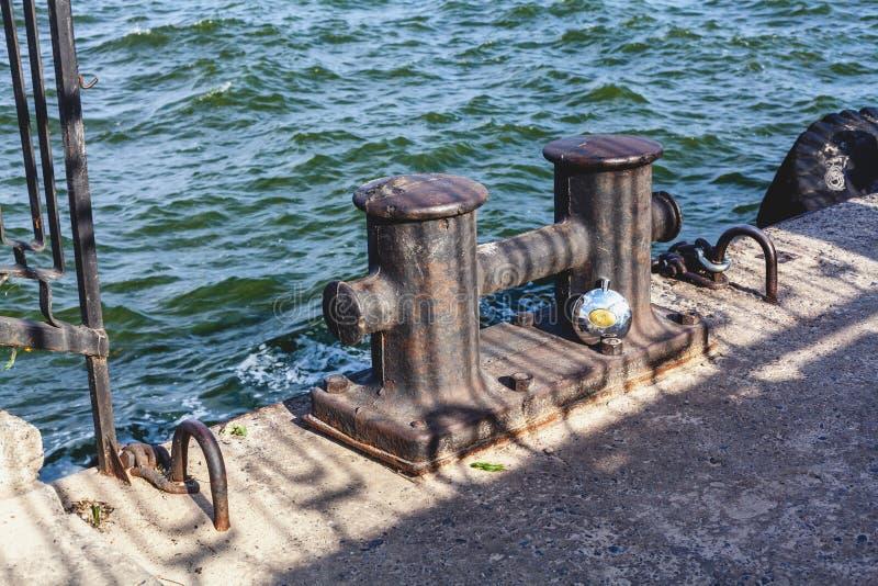 La borne de fer de doubles et le pot rond sur la mer concrète amarrent à quai photos stock