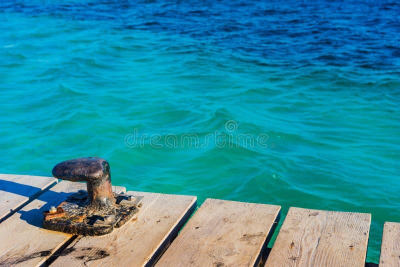 La borne nautique à la jetée en bois au port avec la mer calme ondule photographie stock