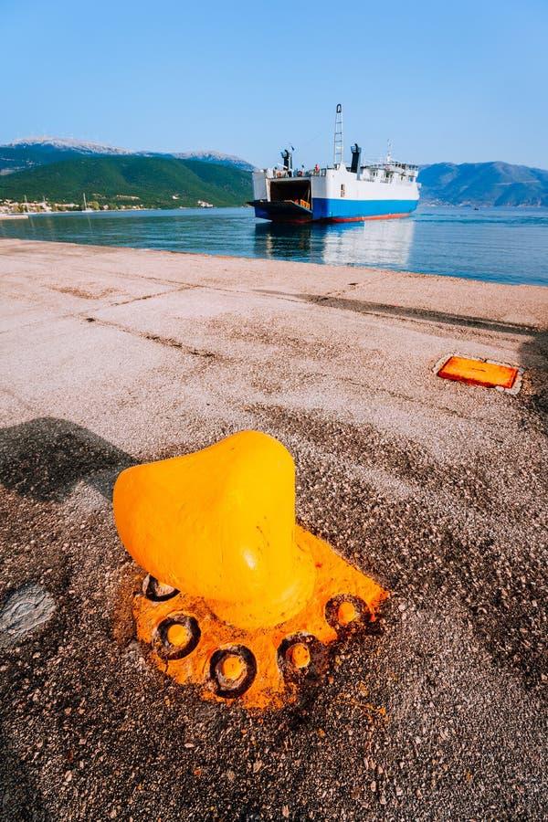 La borne orange d'amarrage et le grand ferry-boat avec des passagers et des voitures arrive belle île grecque Vacances d'été photos libres de droits