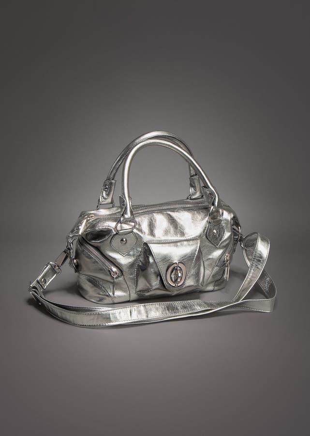 La borsa/borsa d'argento ha fatto di cuoio sul fondo grigio di pendenza fotografia stock