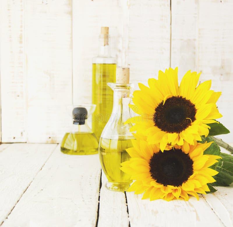 La botella con aceite florece el girasol, foco selectivo foto de archivo