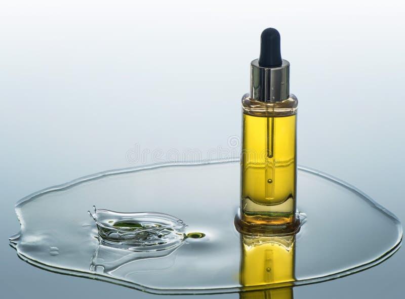 La botella de aceite cosmético se coloca en el fondo del agua con el chapoteo fotos de archivo libres de regalías