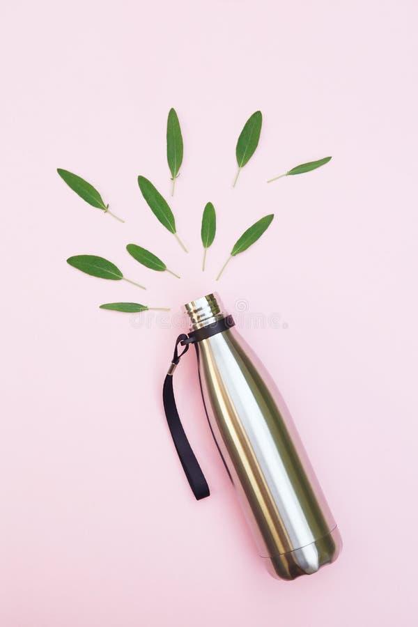 La botella de agua del metal y las hojas verdes aisladas en el fondo rosado, visión superior, van verde, protección del medio amb fotografía de archivo libre de regalías