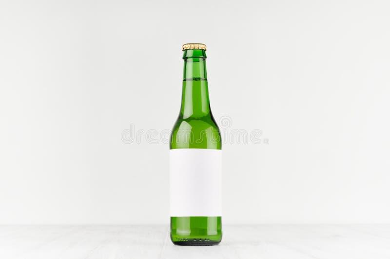 La botella de cerveza verde del longneck 330ml con la etiqueta blanca en blanco en el tablero de madera blanco, imita para arriba imagenes de archivo