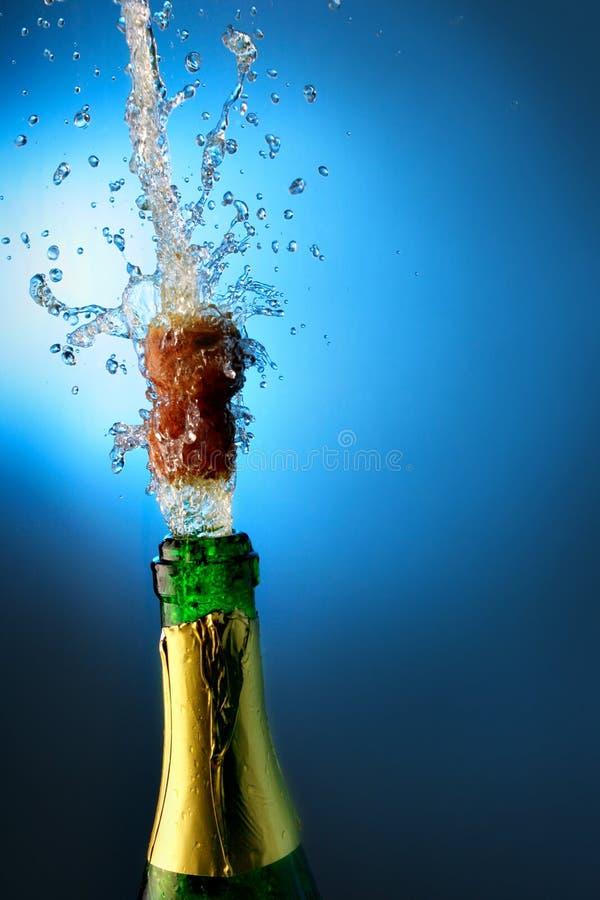 La botella de champán con salpica imagen de archivo libre de regalías