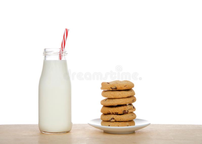 La botella de leche con la paja al lado de la placa con las galletas de microprocesador de chocolate estacó imagen de archivo