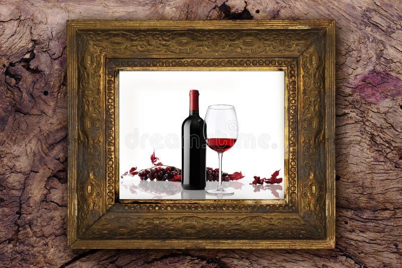 La botella de vino con el vidrio y el manojo de uvas rojas en viejo marco de madera clásico talló a mano en el fondo de madera fotografía de archivo