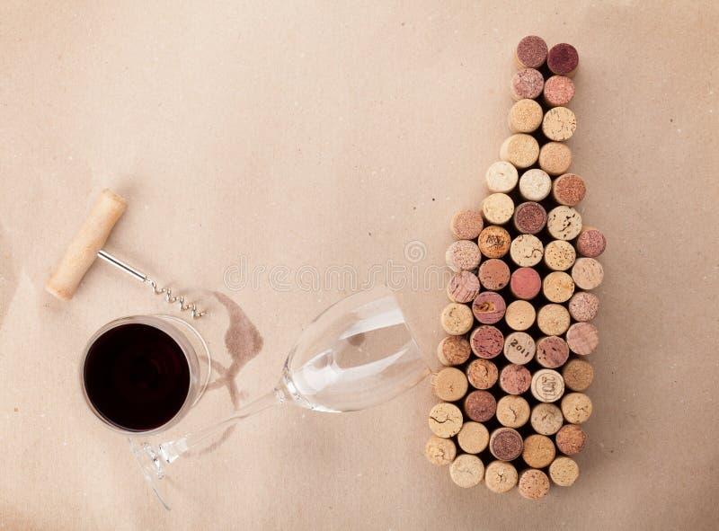 La botella de vino formó corchos, el vidrio de vino y el sacacorchos foto de archivo libre de regalías