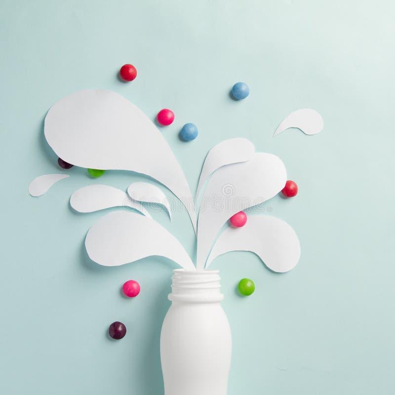 La botella del yogur con salpica y las vitaminas foto de archivo