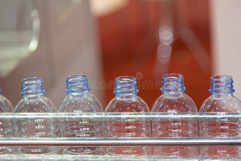 La botella plástica en la banda transportadora fotografía de archivo
