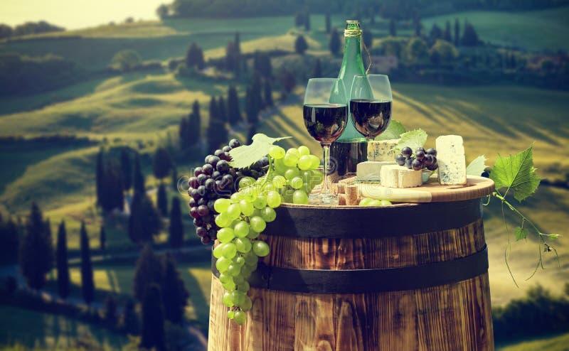 La botella y la copa de vino de vino rojo encendido wodden el barril Fondo hermoso de Toscana fotografía de archivo