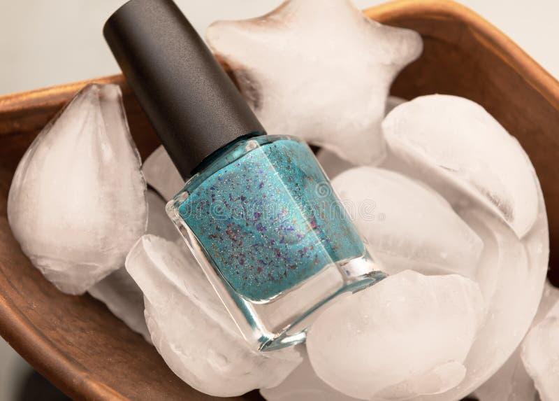 La botella y el hielo del esmalte de uñas con las cáscaras del mar forman imagen de archivo libre de regalías