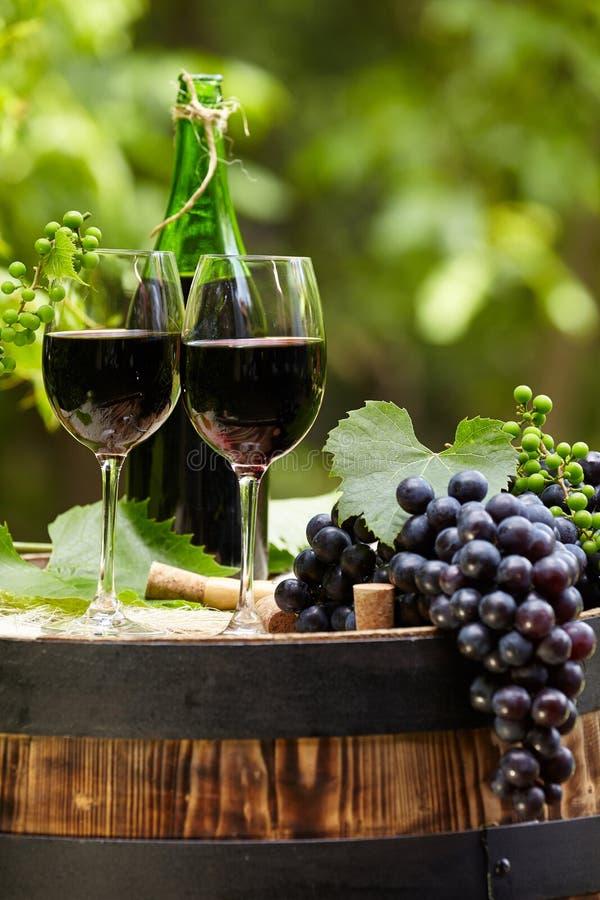 La botella y el vidrio de vino rojo encendido wodden el barril fotografía de archivo