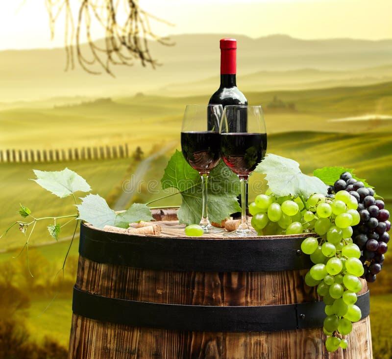 La botella y la copa de vino de vino rojo encendido wodden el barril Tusca hermoso imagen de archivo libre de regalías
