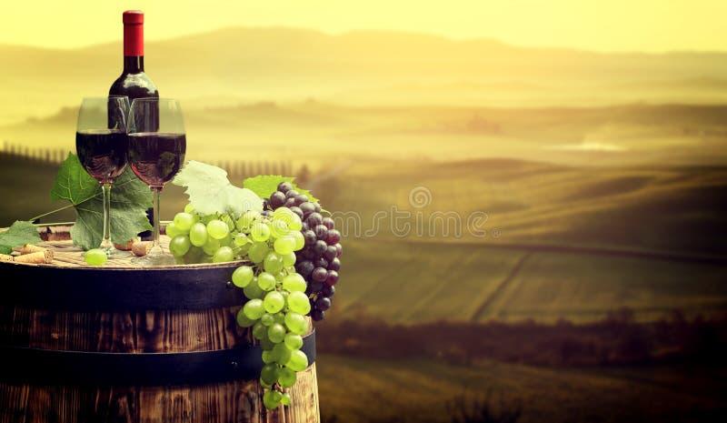 La botella y la copa de vino de vino rojo encendido wodden el barril Tusca hermoso fotografía de archivo