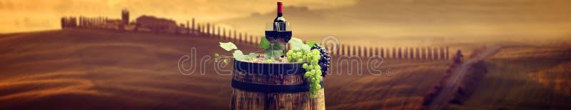 La botella y la copa de vino de vino rojo encendido wodden el barril Tusca hermoso foto de archivo